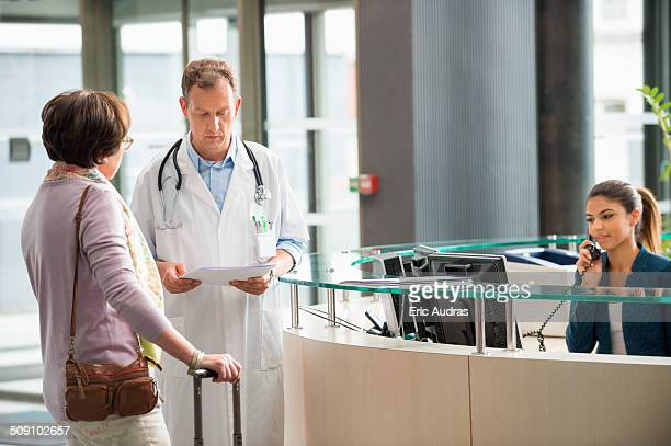 Male doctor discussing with his patient at hospital reception desk