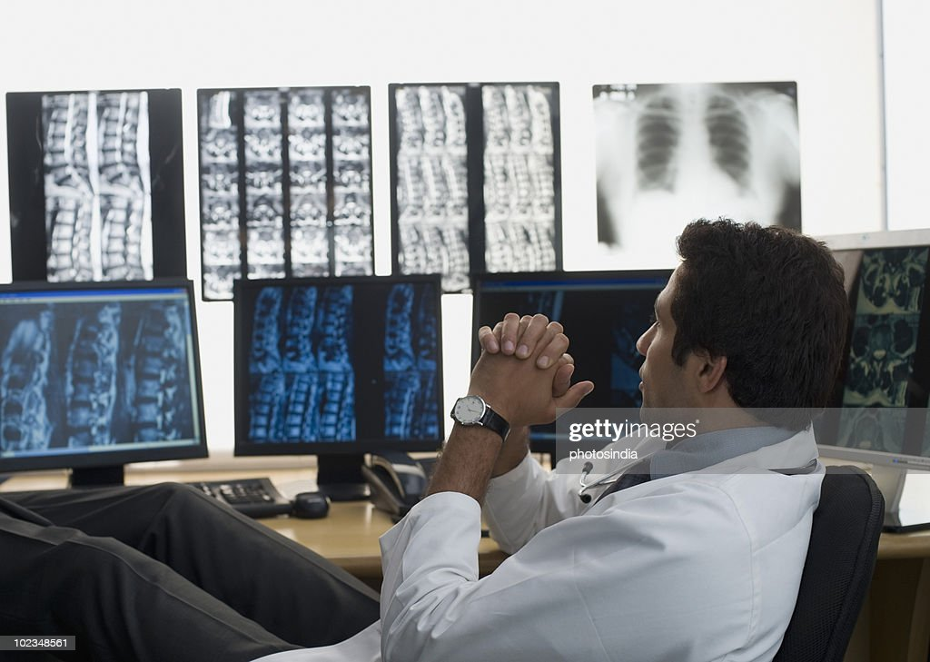 Male doctor examining an X-Ray report : Stock Photo