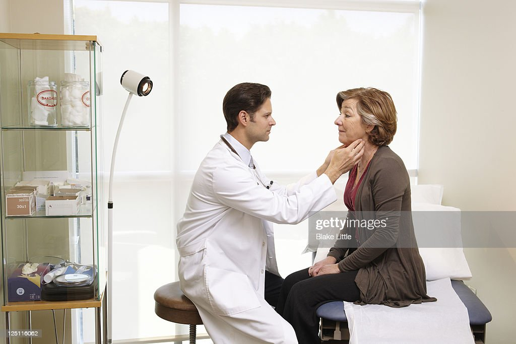 Male Doctor Exams Female Patient : Stock Photo
