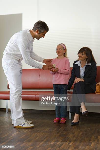 Male doctor giving a gift to a girl with a young woman sitting on a couch beside her