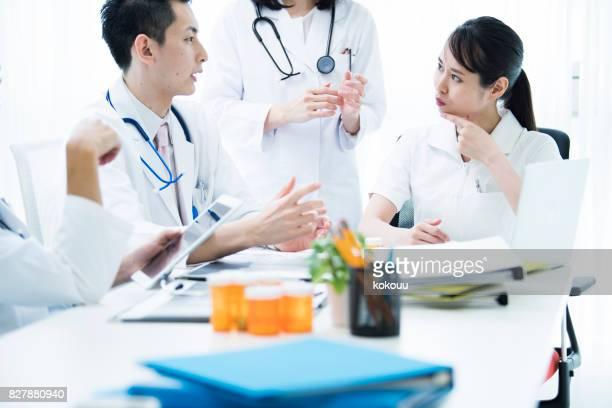 Ein männlicher Arzt spricht mit einer Krankenschwester.