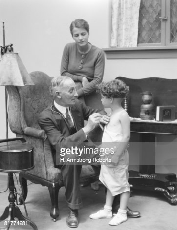 Male doctor making house call, holding stethoscope to chest of little boy patient, mother looking on. : Stock Photo