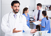 Portrait of confident male doctor meeting patient in medical office