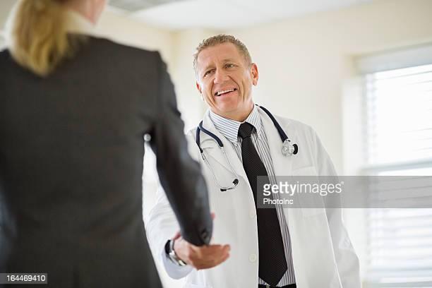 雄医師手を振るビジネスウーマン