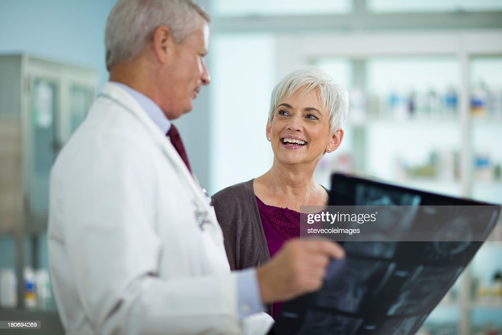 Male Doctor Showing X-Ray Image To Cheerful Mature Woman : Stock Photo