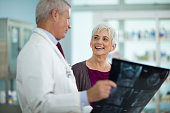 Male Doctor Showing X-Ray Image To Cheerful Mature Woman