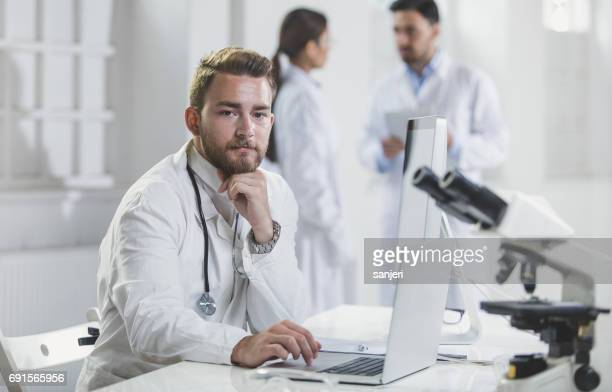 Male Doctor Sitting in His Office With Colleagues Behind