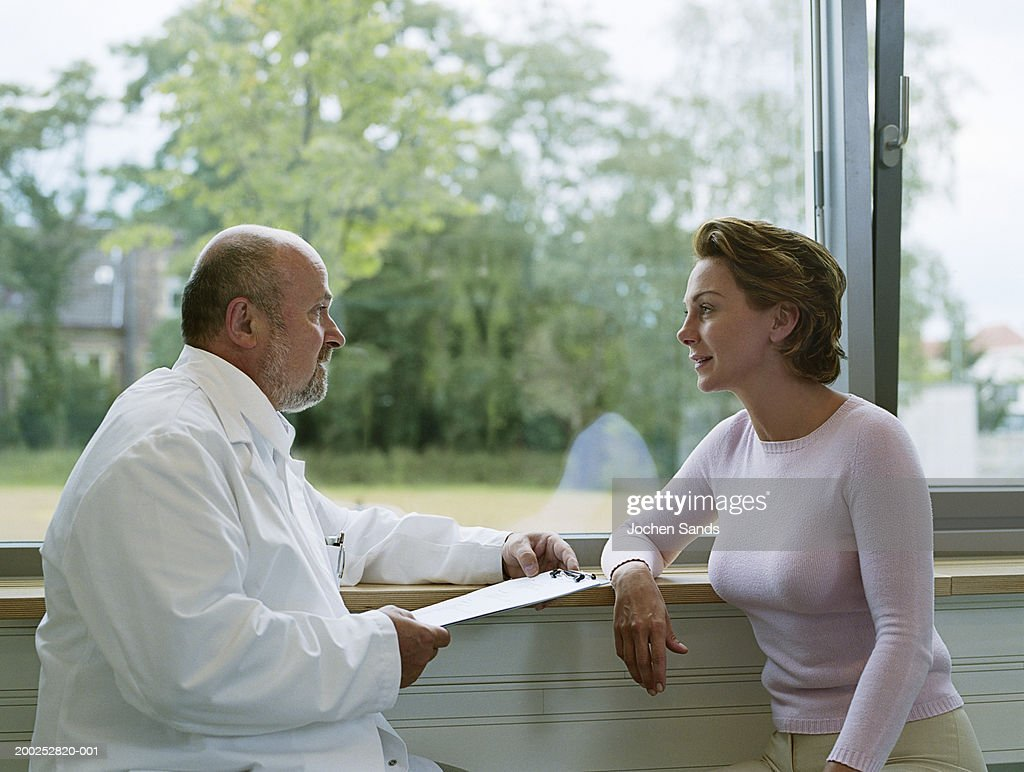 Male doctor sitting with female patient by window, side view : Stock Photo
