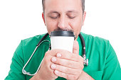 Male doctor smelling fresh coffee from a disposable cup in his break