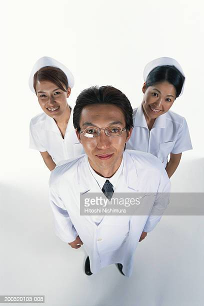 Male doctor standing with two female nurses, elevated view