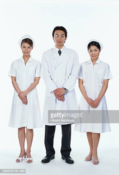 Male doctor standing with two nurses, portrait