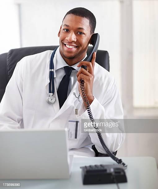 Männlichen Arzt Gespräch am Telefon und mit einem Lächeln