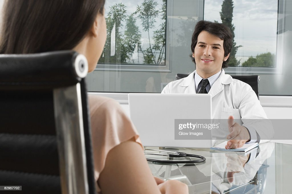 Male doctor talking to a woman in a clinic : Stock Photo