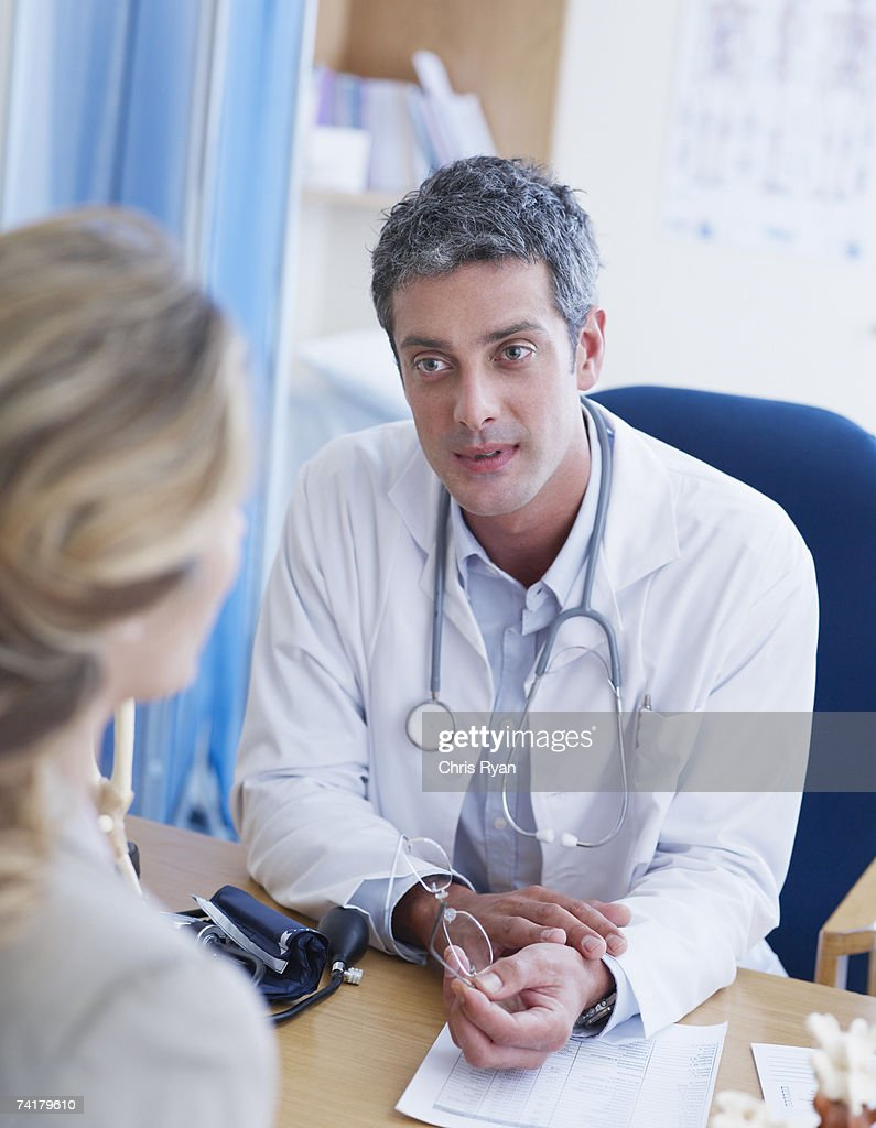 Male doctor talking to woman : Stock Photo