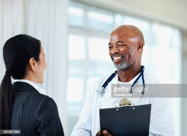 Male doctor talking with his colleague and smiling