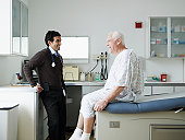 Male doctor talking with senior patient in medical room