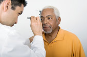 Mature male doctor testing an African American patient's eye in clinic