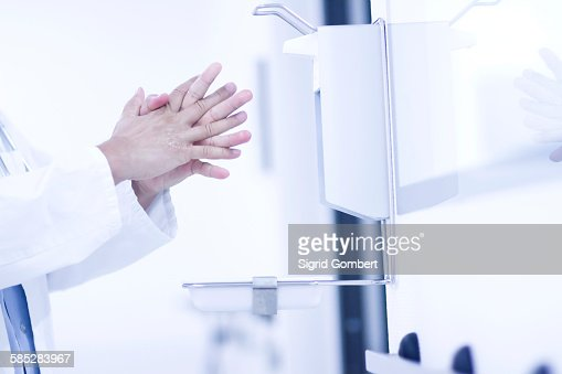 Male doctor using hand sanitizer