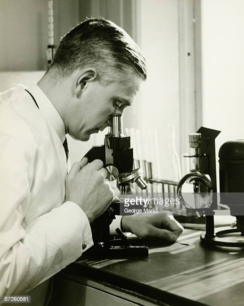 Male doctor using microscope in surgery, (B&W)
