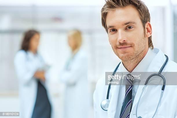 Männlichen Arzt mit Kollegen im Hintergrund