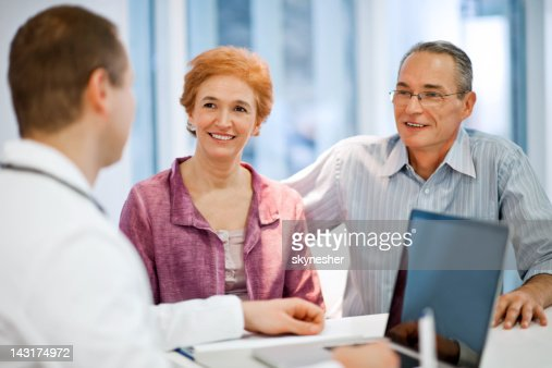 Male doctor with his mature couple patient : Stock Photo