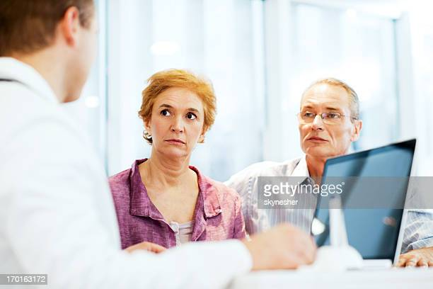Male doctor with his mature couple patient