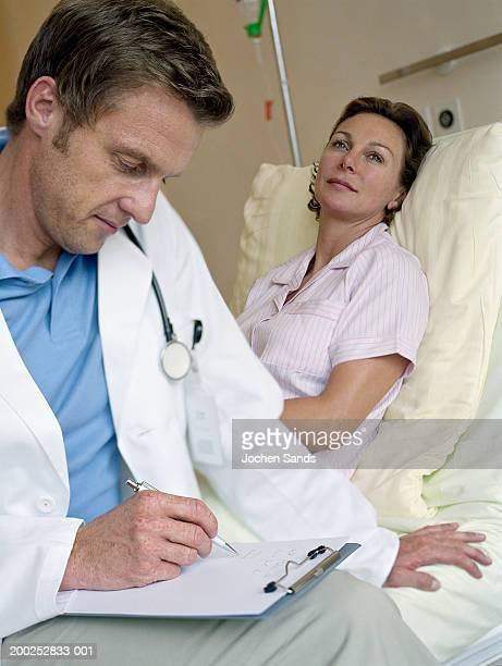 Male doctor writing on clipboard by female patient in hospital bed