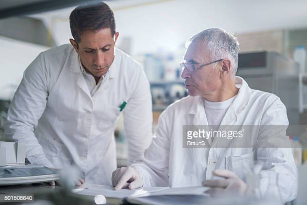 Male doctors cooperating while working together on medical data.