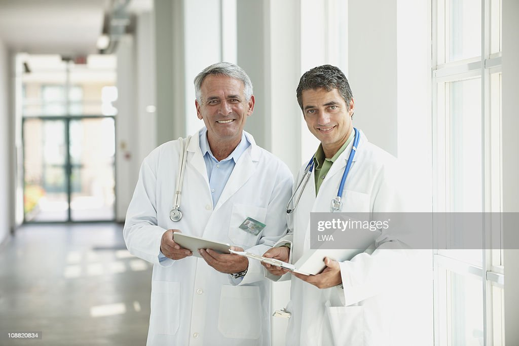 Male Doctors Holding Digital Tablet, Charts : Stock Photo