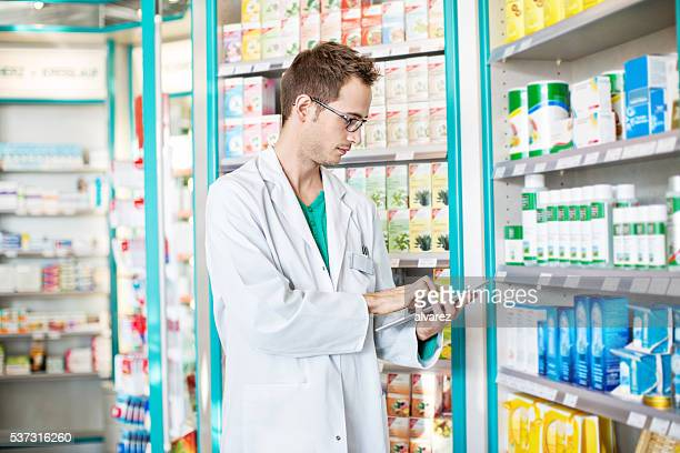 Male druggist using digital tablet at chemist store