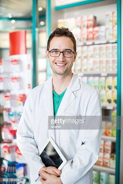 Male druggist with digital tablet at chemist store aisle