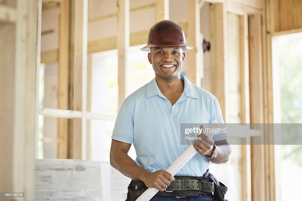 Male Engineer Holding Blueprint At Construction Site : Stock Photo