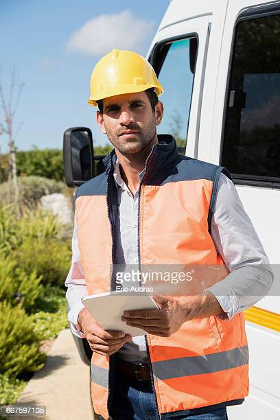 Male engineer with a digital tablet standing by van