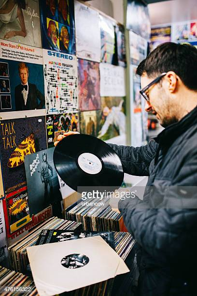 Male examining a second hand vinyl record, record store