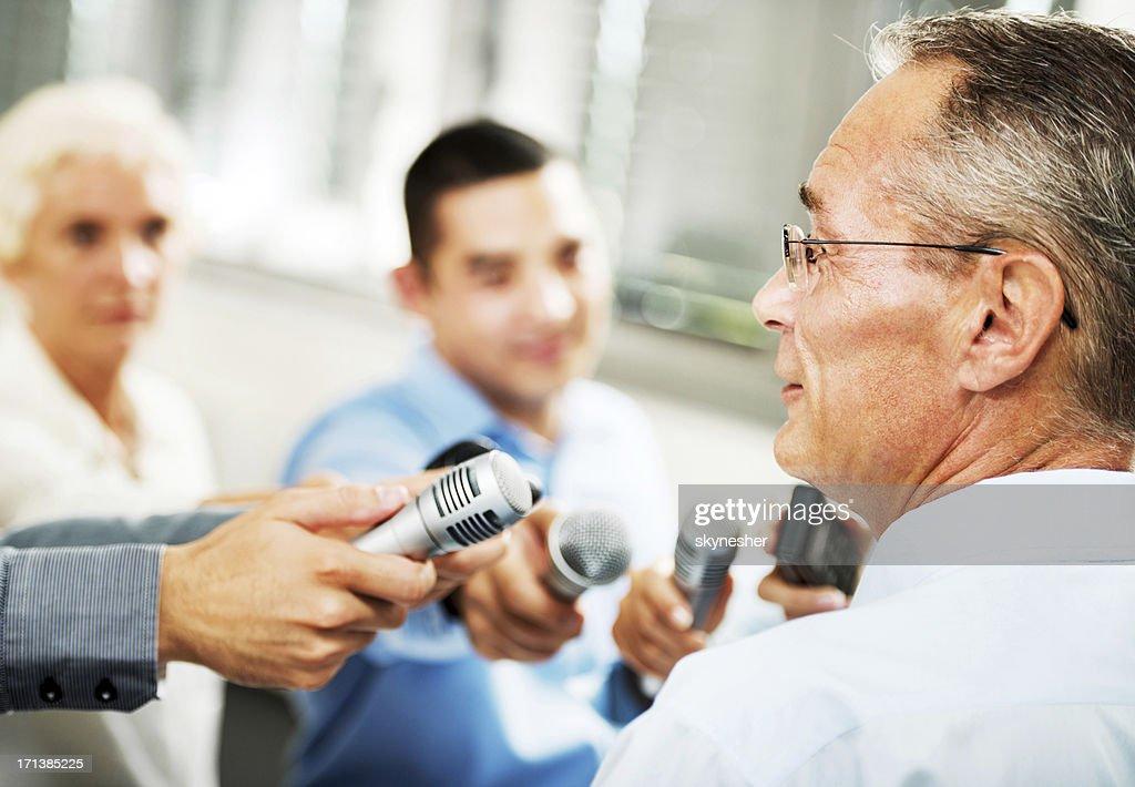 Executivo masculino em causa os jornalistas : Foto de stock