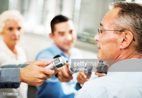 Male executive being questioned by journalists : Stock Photo