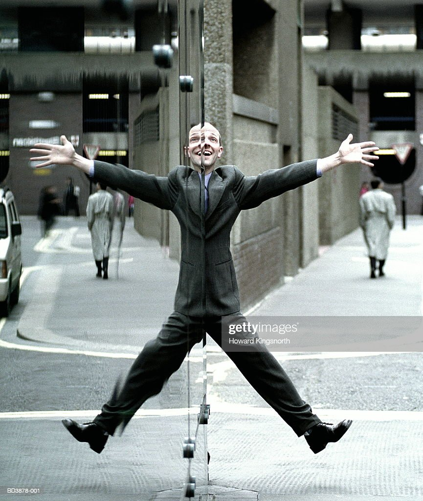 Male executive doing star jump, reflection in window : Stock Photo