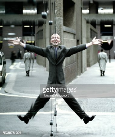 Male executive doing star jump, reflection in window