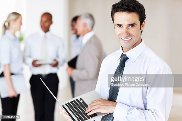 Männliche executive holding laptop