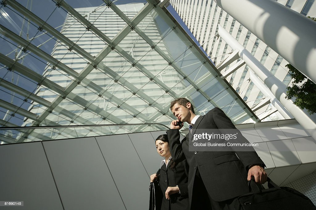 Male executive holding mobile phone with female executive standing next to him, low angle view : Stock Photo
