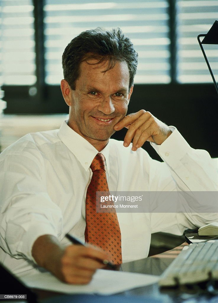 Male executive sitting at desk in office, smiling : Stock Photo