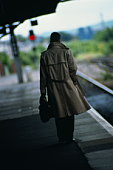Male executive standing on railway station platform, rear view