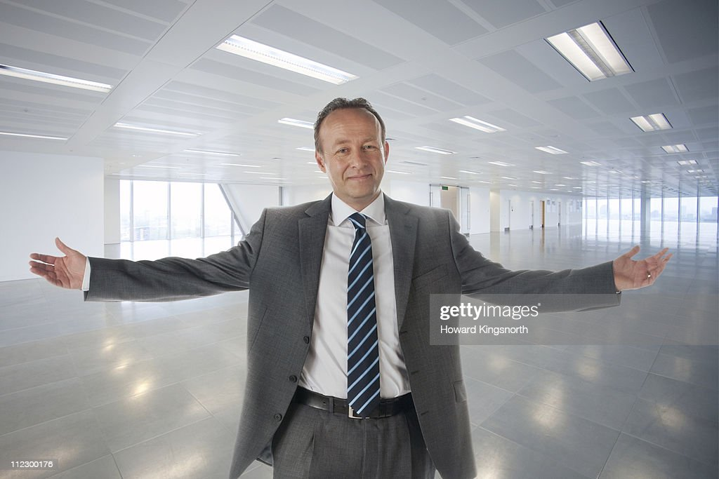 male executive standing with arms outstretched in : Stock Photo