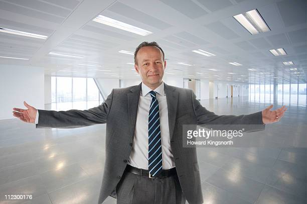 male executive standing with arms outstretched in