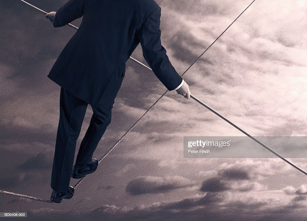 Male executive walking on slack tightrope, rear view (Composite)