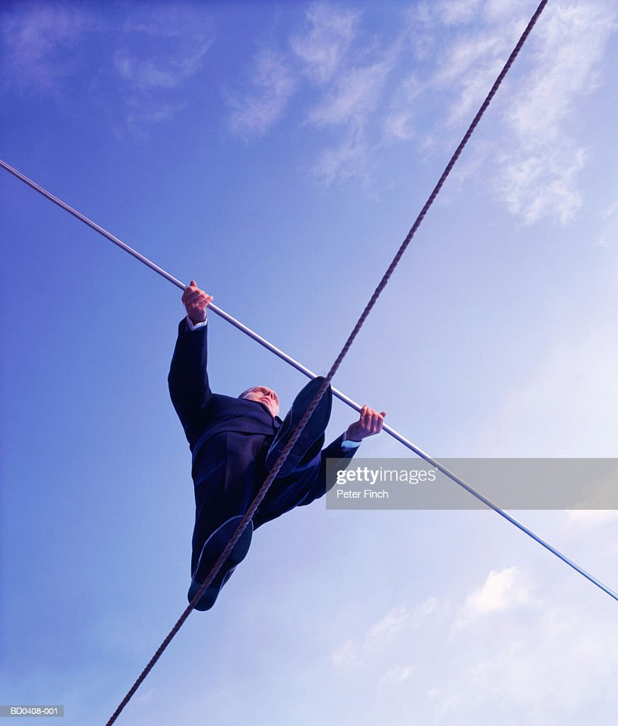 Male executive walking on tightrope, upward view