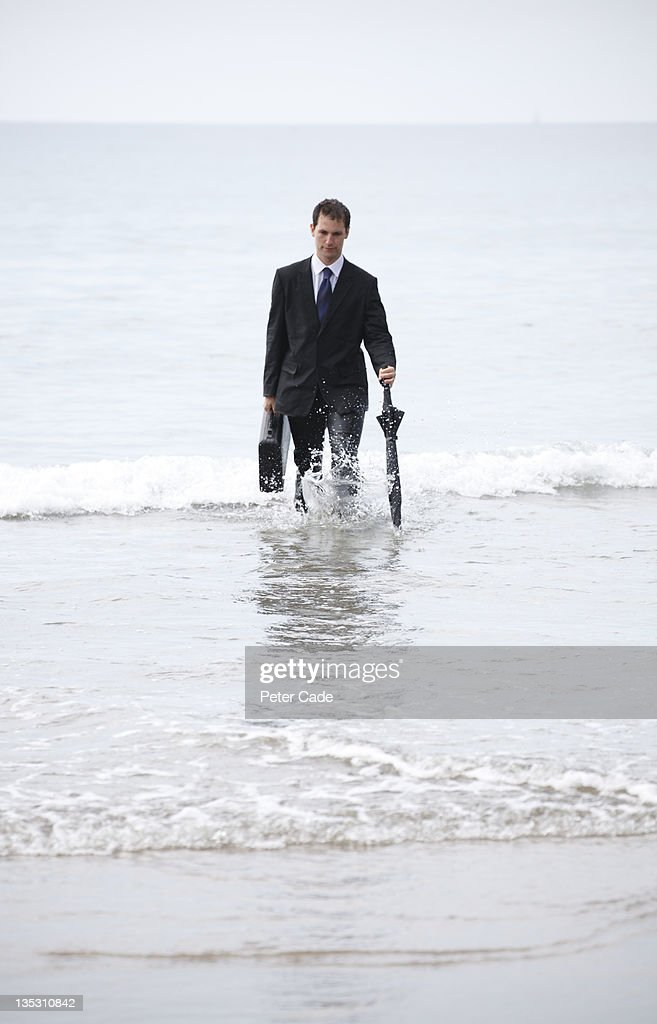 male executive walking out of sea : Stock Photo