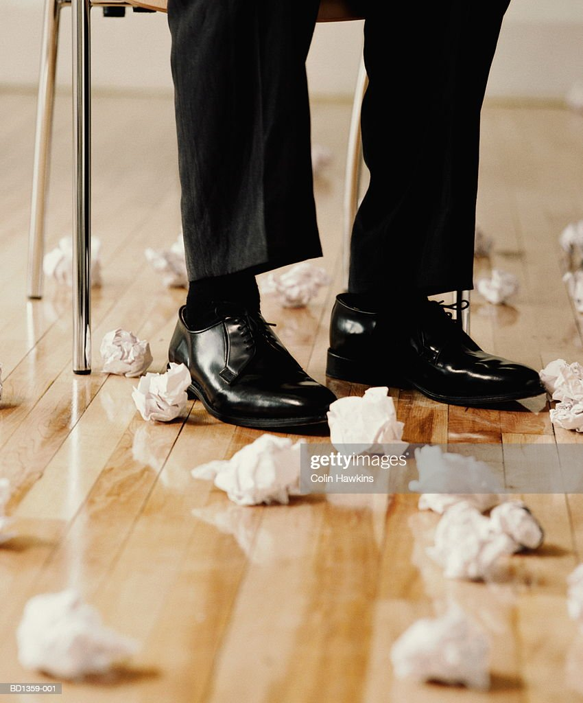Male executive's feet surrounded by screwed-up paper balls,low section