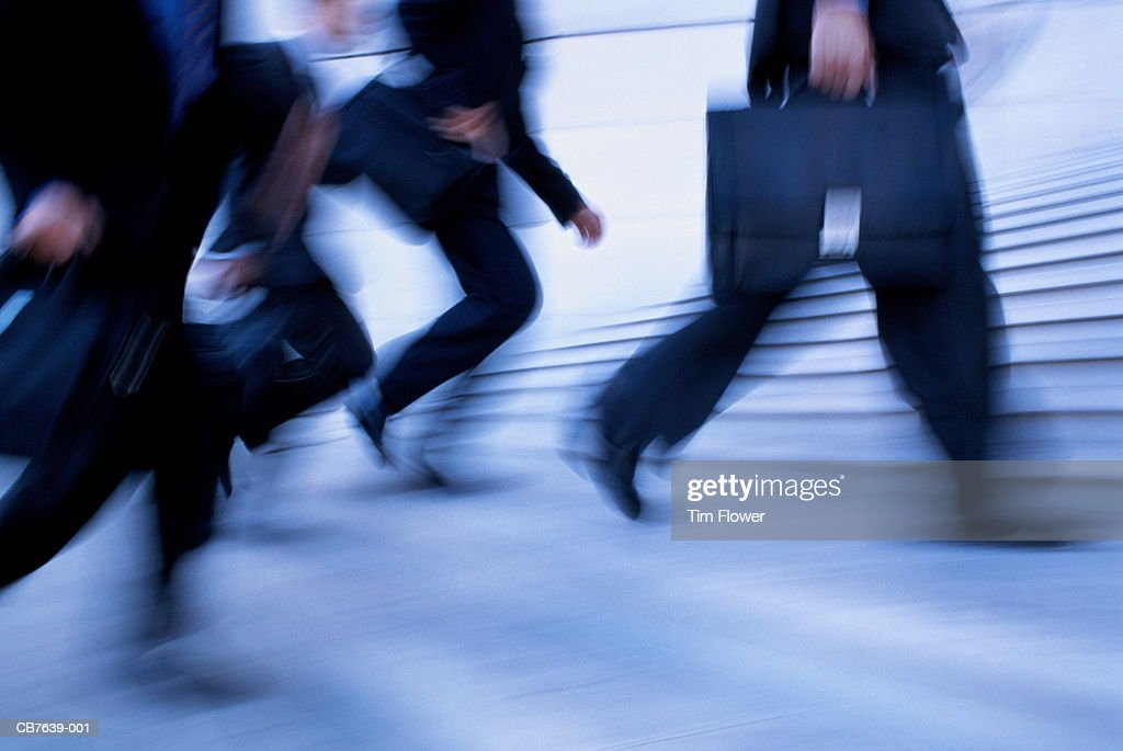 Male executives running up steps, low section (blurred motion) : Stock Photo