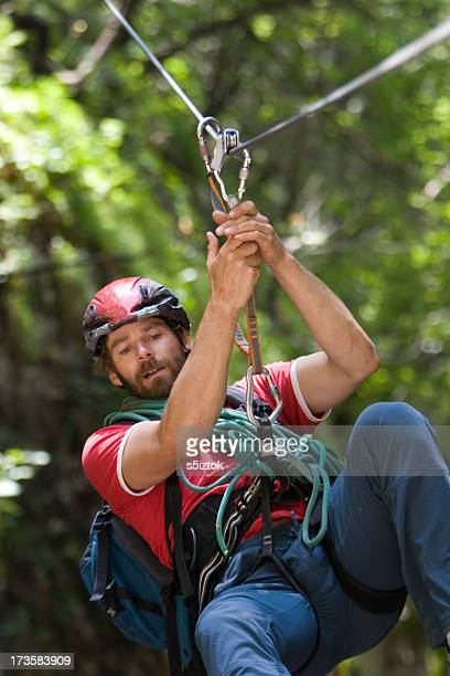 Male extreme sports enthusiast zip lining through forest
